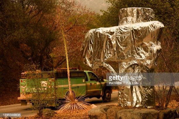 Forest Service vehicle drives past the Sequoia National Park historic park entrance sign wrapped in fire resistant foil along Generals Highway during...