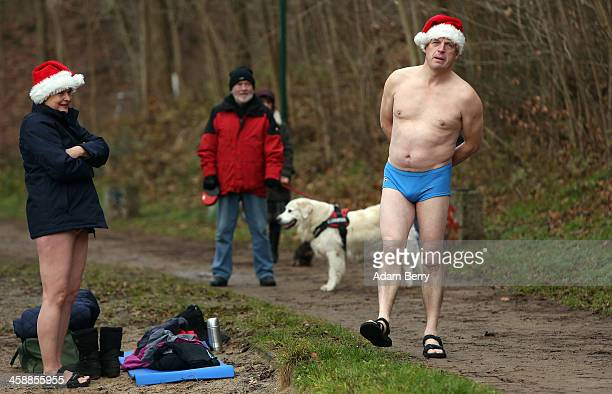 Forest walkers look at an ice swimmer they stumbled across next to the Obersee in Lanke about 50 kilometers north of Berlin on December 22 2013 in...