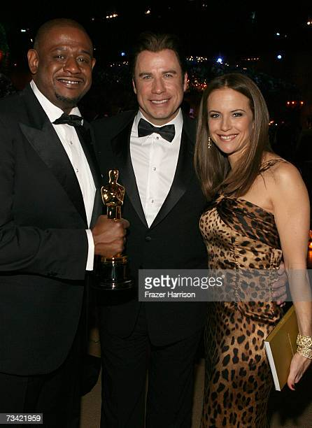 Forest Whitaker poses with his award for Best Actor with actors John Travolta and Kelly Preston at the Governor's Ball after the 79th Annual Academy...