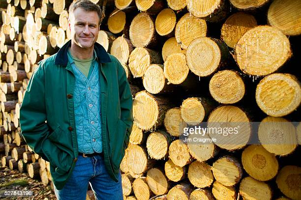 Forester in Front on Stacked Logs
