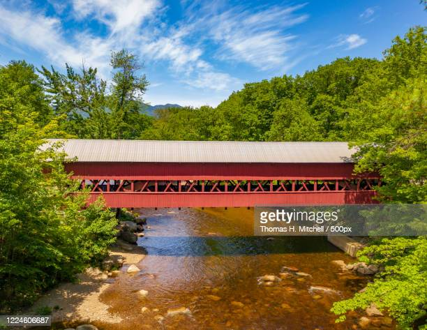 forestland with covered bridge on river, conway, new hampshire, usa - covered bridge stock pictures, royalty-free photos & images