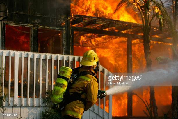US forestry firefighter cools a burning modular home to protect a nearby structure in Deerhorn Valley as the Harris Fire continues growing beyond...