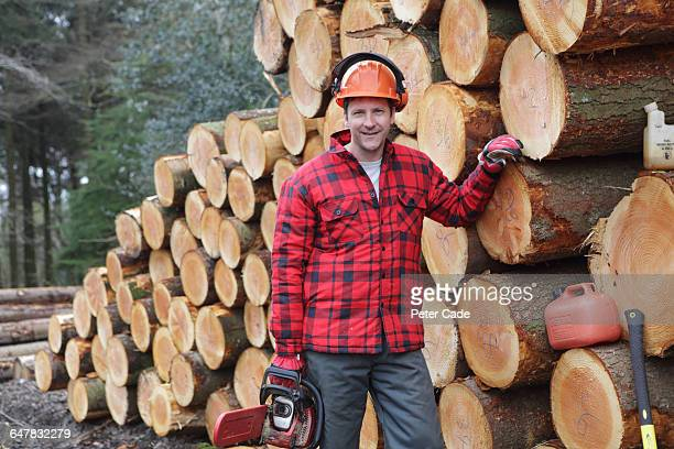 Forestry worker stood next to felled trees