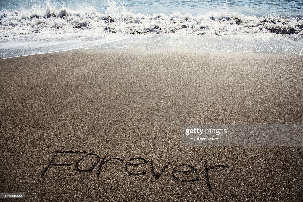 'Forever' written in sand on beach : Stockfoto