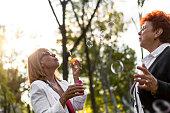 senior woman blowing soap bubbles smiling