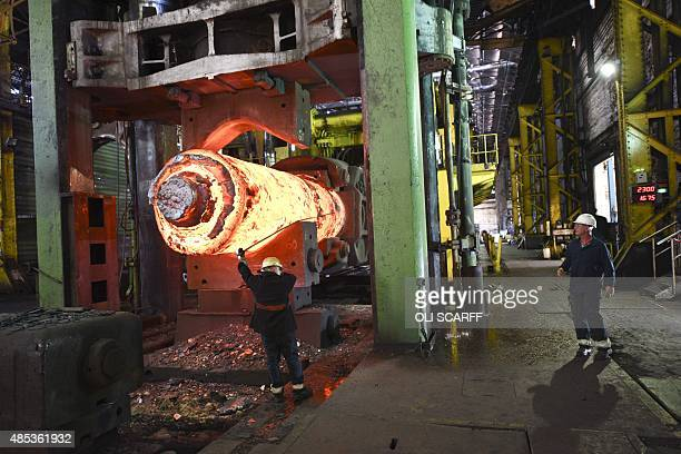 Forgemen oversees the manipulation of a 100 tonne cylinder of of freshly cast hot steel in the forge at Sheffield Forgemasters International Ltd. In...