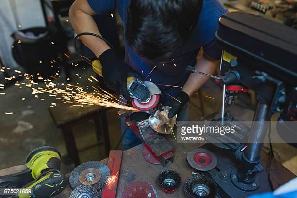 Forger grinding metal in workshop
