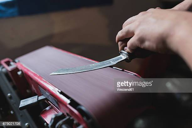 Forger sharpening knife in workshop