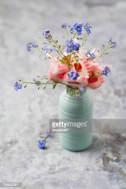 Forget-me-not and heart-shaped lollipops in a vase