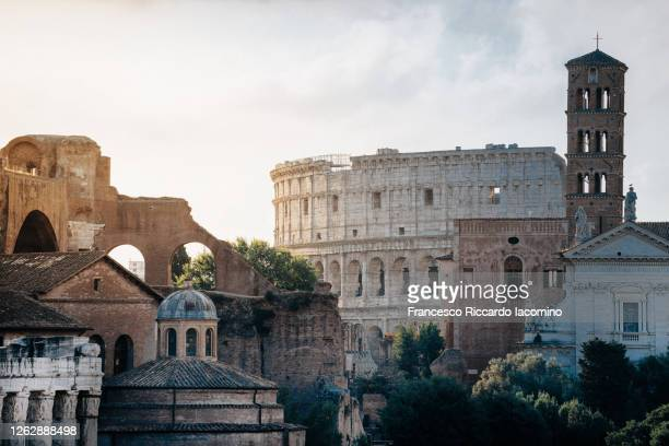 fori imperiali (roman forum), ruins of the ancient roman empire and coliseum on background. unique perspective. rome, lazio, italy - rome italy stock pictures, royalty-free photos & images