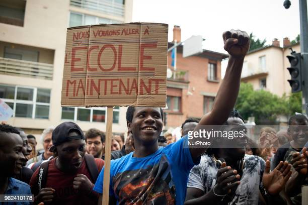 A forign minor holding a placard reading 'We want to go to school now ' raises his fist as they learn the decision from the court Unaccompanied...