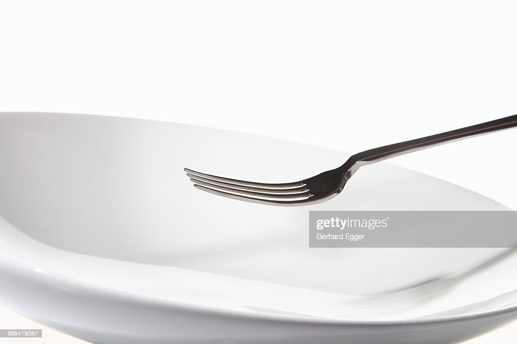 Fork and empty white plate : Stock Photo