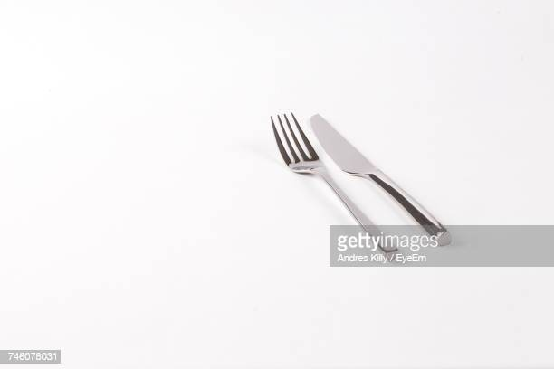 fork and table knife on white background - forchetta foto e immagini stock