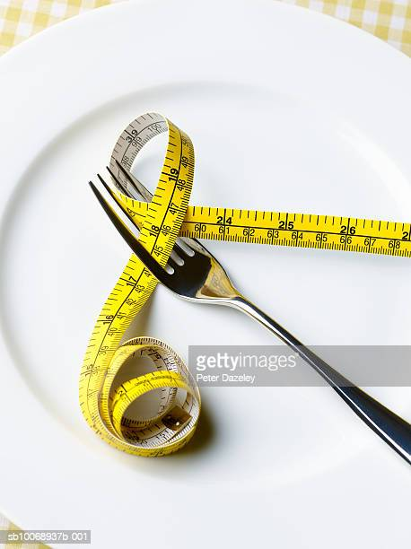 Fork and tape measure on plate, close-up