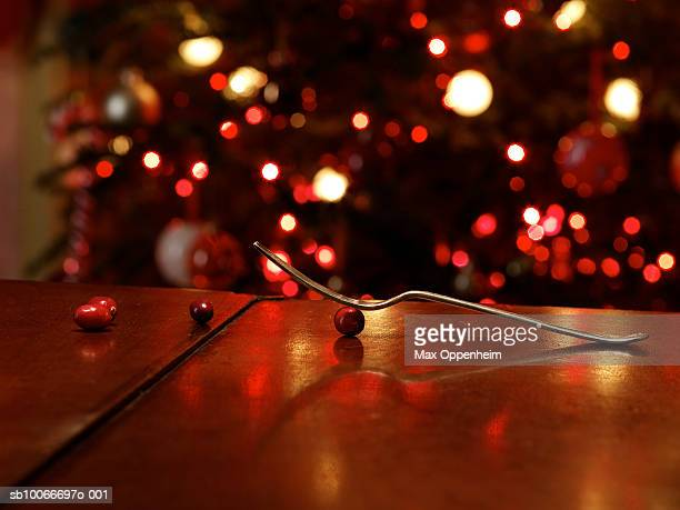 Fork balanced on cranberry in front of Christmas tree