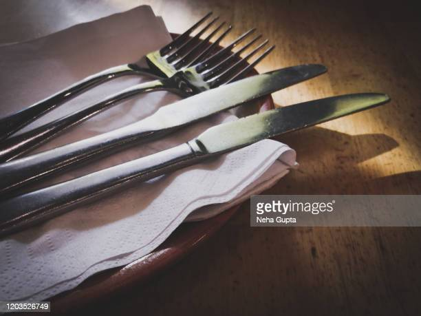 fork & knife on a wooden dining table - daylight studio shot - kitchen knife stock pictures, royalty-free photos & images