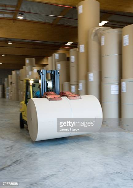 Fork lift carrying roll of paper