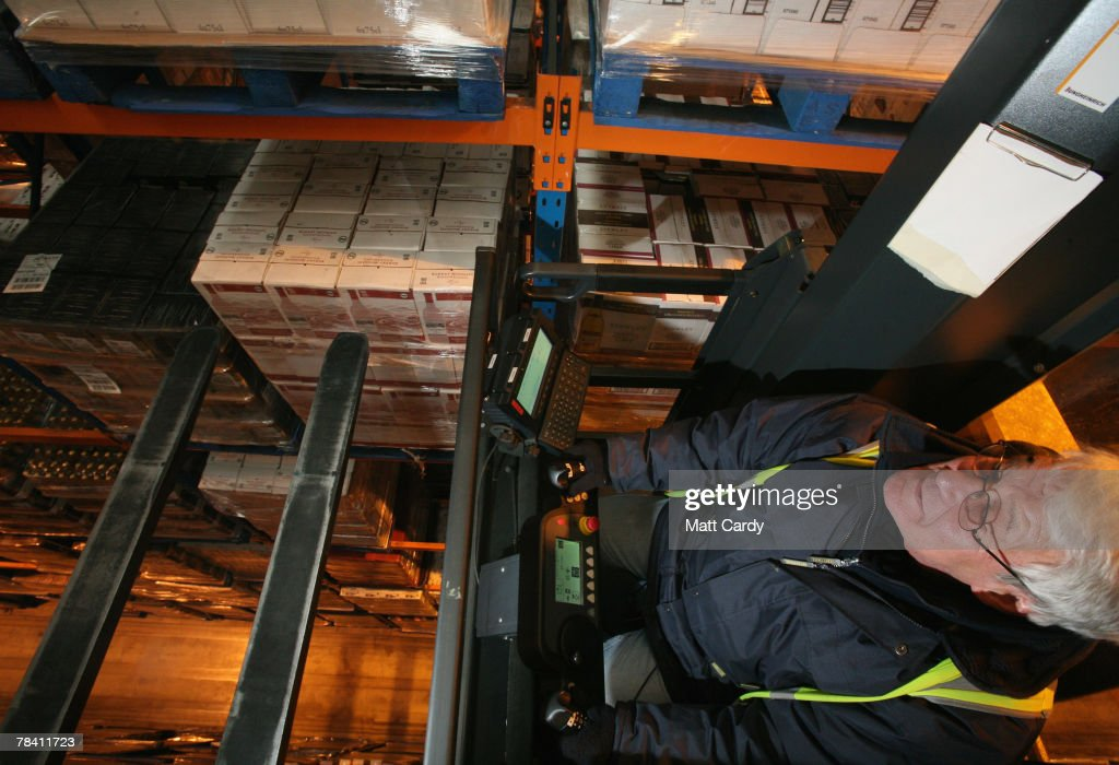 Fork lift crane driver Steve Stiley reaches for a pallet on the top of a rack at the giant distribution centre in Avonmouth on December 12 2007 near Bristol, England. The giant warehouse, owned by Constellation Europe, is currently packed full of pallets of alcohol to be dispatched - with 90per cent destined for the UK - and means a lorry leaving every seven minutes, 24 hours a day, to keep up with demand.