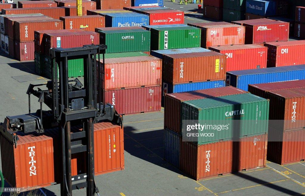 A fork lift (below-L) moves export shipp : News Photo