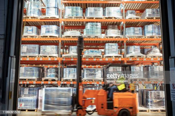 fork lift truck driving past printed food packaging in storage in print factory - plant stock pictures, royalty-free photos & images