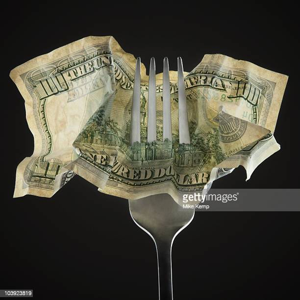 Fork pierced through American 100 dollar bill