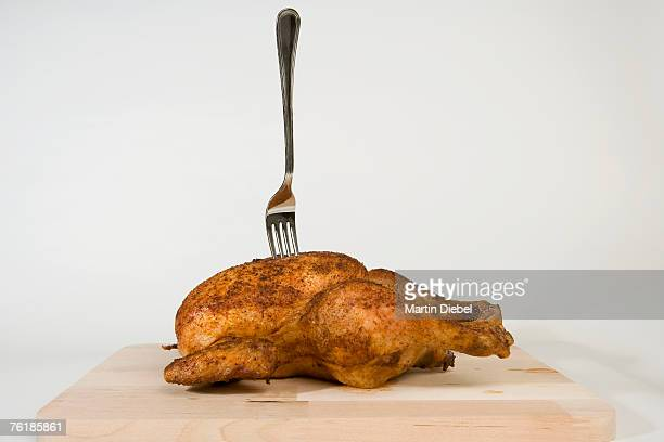 A fork stuck in a roast chicken