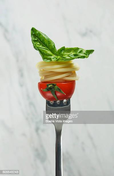 Fork with spaghetti, tomato and basil leaves