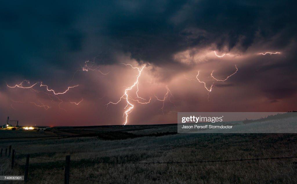Forked lightning in orange sky over rural area, Grant, Nebraska, United States, North America : Stockfoto