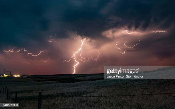 Forked lightning in orange sky over rural area, Grant, Nebraska, United States, North America