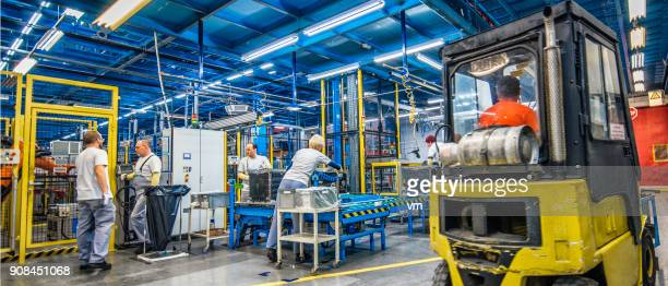 Forklift and manual workers in a factory