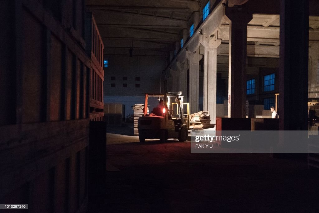 A forklift carries away parts of Ai Weiwei's artwork as his 'Left and Right Art Studio' is demolished in Beijing on August 3, 2018. - Ai Weiwei said on August 3, 2018 wrecking crews had started demolishing his main studio in Beijing without notice, three years after the artist and government critic left China.