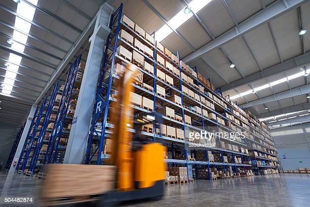 Forklift carrying cardboard box in warehouse.