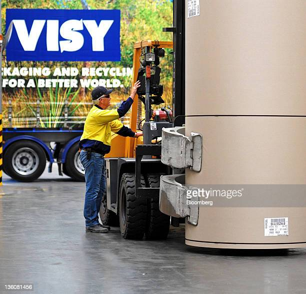 A forklift driver moves a reel of recycled paper in the reel store of the Visy Industries Holdings Ltd recycling plant in Brisbane Australia on...