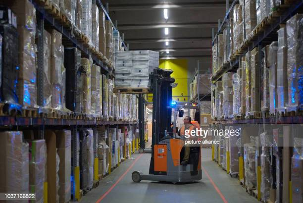Forklift driver Pavel Fiala gets a palate of goods from a shelf at the warehouse of the Amazon logistics centre in Werne Germany 12 November 2015 The...