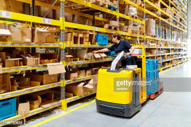 forklift driver reaching for cardboard box - industrial storage bins stock pictures, royalty-free photos & images