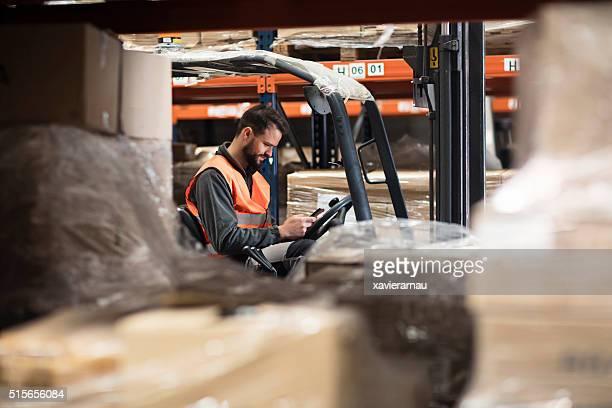 Gabelstapler-Fahrer, Sie lesen eine Befehl Hinweis auf dem Mobiltelefon