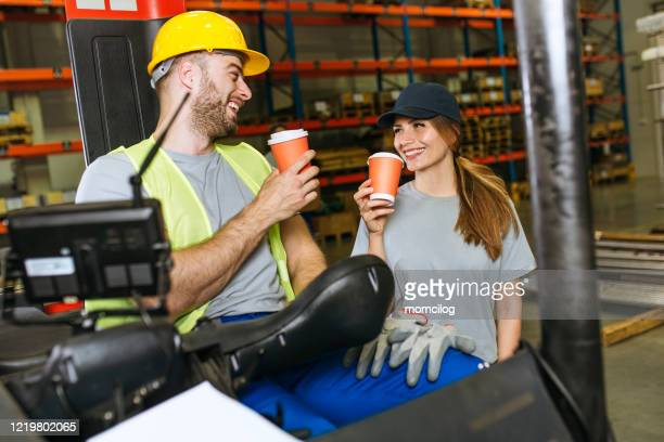 forklift driver talking pause to drink coffee with supervisor inside factory storage unit - coffee drink stock pictures, royalty-free photos & images