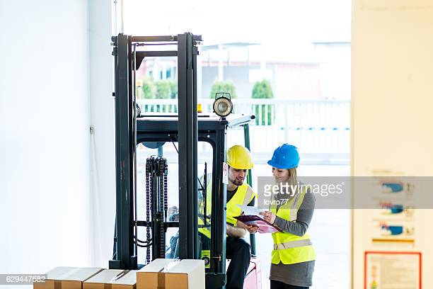 Forklift driver talking to a manager in the warehouse