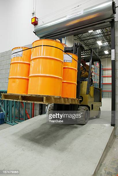 forklift in warehouse carrying yellow barrel