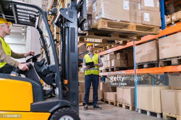 forklift lifting load in a warehouse - rack stock pictures, royalty-free photos & images
