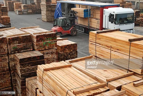 Forklift loading boards in a lumberyard
