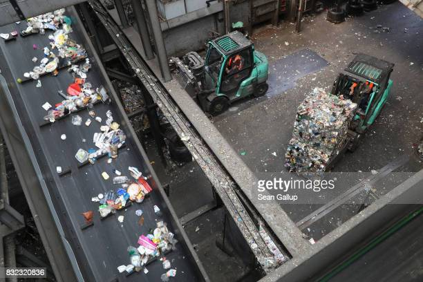 A forklift moves a bale of sorted materials as plastics flow by on a conveyor at the ALBA sorting center for the recycling of packaging materials on...