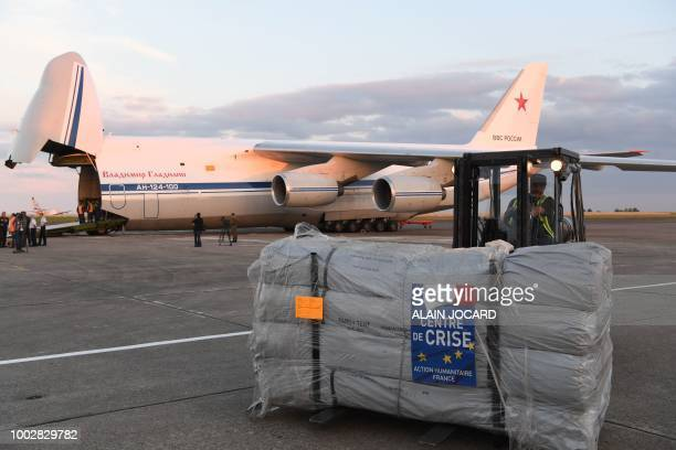A forklift moves humanitarian supplies to be loaded onto Russian military officer stands by as an Antonov An124 Ruslan Widebody at the former...