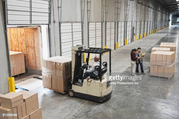 forklift moving boxes onto truck at loading dock of warehouse - loading dock stock pictures, royalty-free photos & images