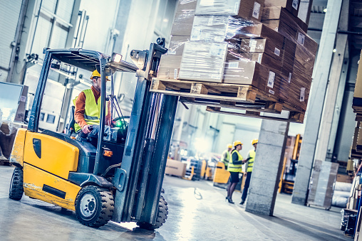 Forklift moving stack of boxes 909987026