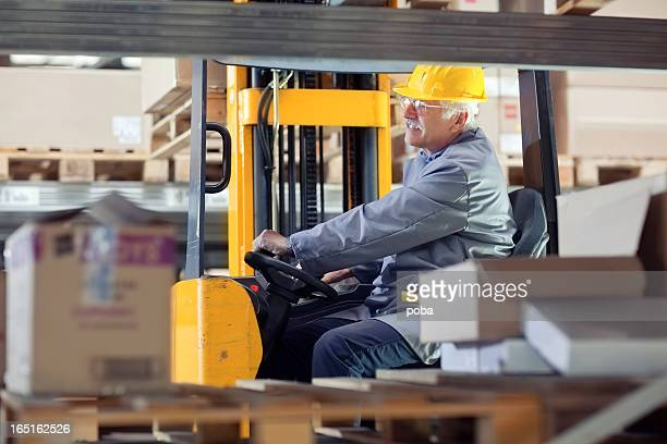 forklift operator at warehouse Loading, lifting cardboard boxes on pallet