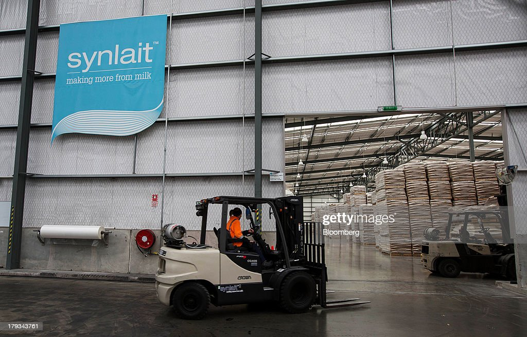A forklift operator drives past the Synlait Milk Ltd. logo displayed inside the warehouse at the company's manufacturing plant in the town of Rakaia, 60km from Christchurch, New Zealand, on Friday, Aug. 30, 2013. Synlait, a unit of Shanghai-based Bright Dairy & Food Co., will process more milk than forecast in 2013-14, the company announced on Aug. 30. Photographer: Brendon O'Hagan/Bloomberg via Getty Images