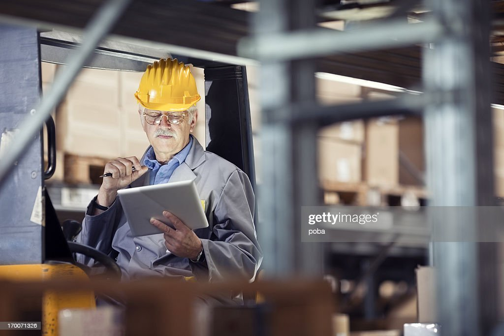 Forklift operator looking at a digital tablet stock photo getty images forklift operator looking at a digital tablet stock photo publicscrutiny Image collections