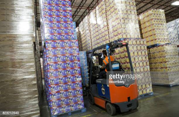 A forklift operator moves boxes of Huggies brand diapers in the warehouse of the KimberlyClark Corp manufacturing facility in Paris Texas US on Oct...