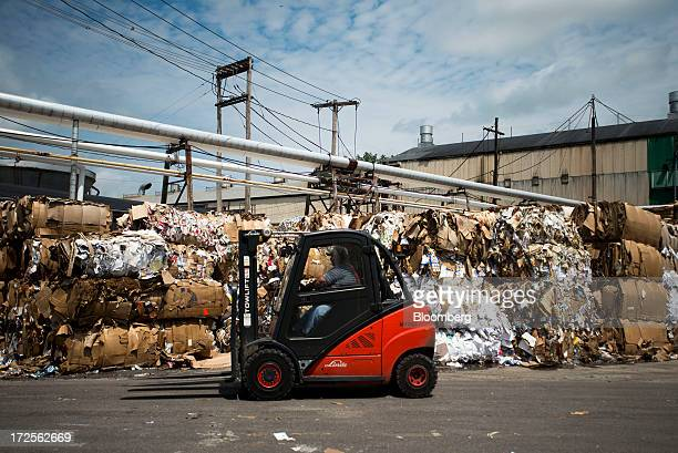 A forklift operator moves bundles of recycled paper and cardboard in the collection area at Newark Recycled Paperboard Solutions in Baltimore Ohio US...